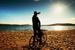 Силуэт велосипедиста молодого человека на предпосылке голубого неба и захода солнца на пляже Конец сезона на озере Стоковые Фото