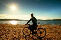 Силуэт велосипедиста молодого человека на предпосылке голубого неба и захода солнца на пляже Конец сезона на озере Стоковые Фотографии RF