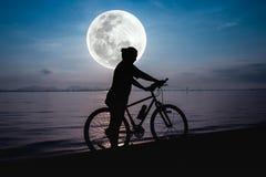 Силуэт велосипедиста наслаждаясь взглядом на взморье outdoors Стоковые Фотографии RF