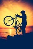 Силуэт велосипедиста наслаждаясь взглядом на взморье outdoors Стоковая Фотография