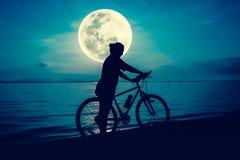 Силуэт велосипедиста наслаждаясь взглядом на взморье outdoors Стоковое Изображение