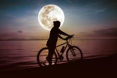 Силуэт велосипедиста наслаждаясь взглядом на взморье outdoors Стоковое Фото