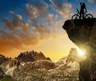 Силуэт велосипедиста на велосипеде на заходе солнца Стоковые Изображения RF