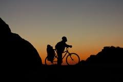 Силуэт велосипедиста на велосипеде дороги на заходе солнца Стоковые Изображения RF