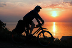 Силуэт велосипедиста на заходе солнца Стоковое Изображение RF