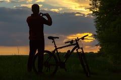 Силуэт велосипедиста на заходе солнца Стоковые Фотографии RF