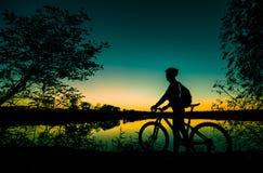Силуэт велосипедиста на заходе солнца Стоковое Фото
