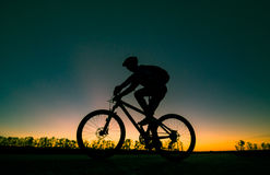 Силуэт велосипедиста на заходе солнца Стоковое фото RF