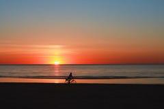 Силуэт велосипедиста на пляже на заходе солнца Стоковая Фотография