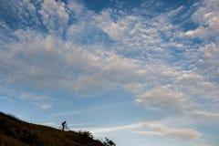 Силуэт велосипедиста по пересеченной местностей идя покатый Стоковые Изображения