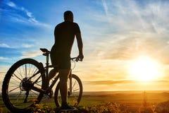 Силуэт велосипедиста стоя с горным велосипедом на холме на заходе солнца Стоковое Изображение RF