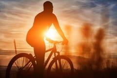 Силуэт велосипедиста стоя с горным велосипедом на холме на заходе солнца Стоковая Фотография