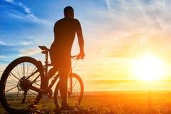 Силуэт велосипедиста стоя с горным велосипедом на холме на заходе солнца Стоковое Фото