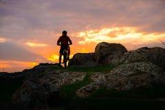 Силуэт велосипедиста с горным велосипедом на следе весны скалистом на красивом заходе солнца Весьма спорт и концепция приключения Стоковое Изображение RF