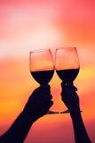 Силуэт вина пар выпивая на заходе солнца Стоковые Изображения