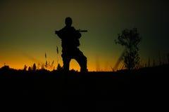 Силуэт воинских солдата или офицера с оружиями на ноче стоковое фото rf