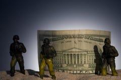Силуэт воинских солдат на предпосылке денег стоковые фото