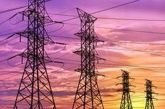 Силуэт высоковольтной линии электропередач возвышается под красочным небом захода солнца Стоковое Изображение RF