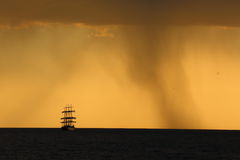 Силуэт высокорослого корабля на заходе солнца Стоковые Фотографии RF