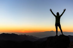 Силуэт в горах, inspi успеха альпиниста женщины достижения Стоковое фото RF