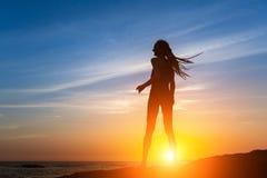 Силуэт гибкой девушки танцев на морском побережье Стоковая Фотография