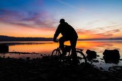 Силуэт горного велосипеда и велосипедиста на восходе солнца Стоковые Фото