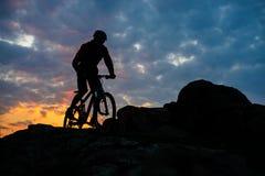 Силуэт горного велосипеда катания велосипедиста на следе весны скалистом на красивом заходе солнца Весьма спорт и концепция прикл Стоковая Фотография RF