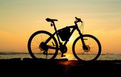 Силуэт горного велосипеда на море с небом захода солнца Стоковое Изображение RF