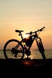 Силуэт горного велосипеда на море с небом захода солнца Стоковое Фото