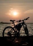 Силуэт горного велосипеда на море с небом захода солнца Стоковое фото RF