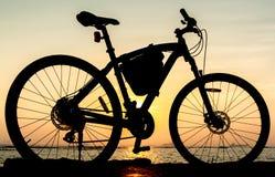 Силуэт горного велосипеда на море с небом захода солнца Стоковая Фотография RF