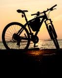 Силуэт горного велосипеда на море с небом захода солнца Стоковые Изображения RF