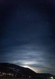 Силуэт горы против звёздного почти неба и сияющей луны стоковое фото