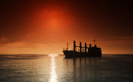 Силуэт грузового корабля над восходом солнца стоковые изображения