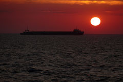 Силуэт грузового корабля на заходе солнца Стоковое Изображение RF
