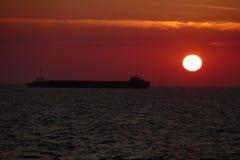 Силуэт грузового корабля на заходе солнца Стоковая Фотография RF
