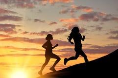 Силуэт 2 девушек бежать конкуренция Стоковое Изображение RF