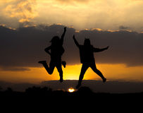 Силуэт 2 девушек скача с красивым заходом солнца стоковое фото rf