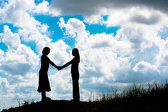 Силуэт 2 девушек смотря на один другого держит руки совместно Стоковые Изображения