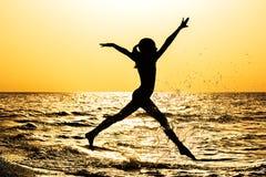 Силуэт девушки, бежать вдоль seashore на заходе солнца Стоковая Фотография RF