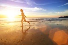 Силуэт девушки бежать на пляже океана Стоковые Изображения