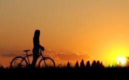 Силуэт девушки велосипедиста горы Стоковое фото RF