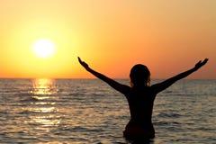 Силуэт девушки в купальном костюме в море на восходе солнца Стоковое Изображение RF