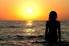 Силуэт девушки в купальном костюме в море Стоковые Изображения RF