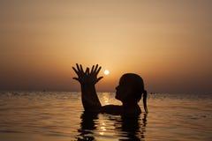 Силуэт девушки в океане на заходе солнца, женщине океана в восходе солнца l Стоковое Изображение