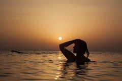 Силуэт девушки в океане на заходе солнца, женщине океана в восходе солнца l Стоковое Фото