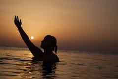 Силуэт девушки в океане на заходе солнца, женщине океана в восходе солнца l Стоковое Изображение RF