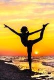 Силуэт девушки в представлении йоги на пляж на заходе солнца Стоковое фото RF