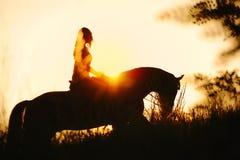 Силуэт девушки ехать лошадь на заходе солнца Стоковая Фотография