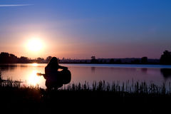 Силуэт девушки играя гитару рекой Стоковые Изображения